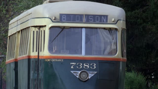 """medium angle of green and yellow trolley or streetcar that reads """"8 towson."""" pans down to wheels grating on pavement and sparks flying, trying to stop. trolley stops at end. neg cut. - anno 1920 video stock e b–roll"""