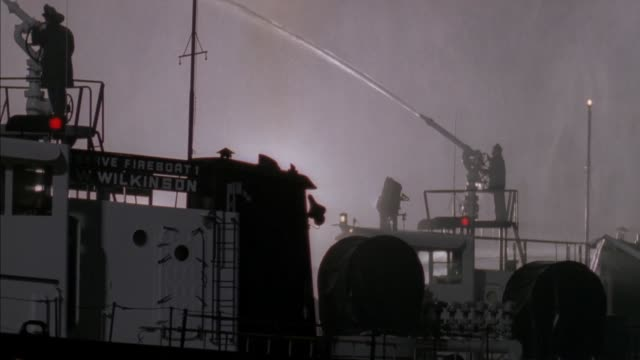 "MEDIUM ANGLE OF FIRE BOAT FIGHTING FIRE. SIGN READS ""RESERVE FIREBOAT WILKINSON."" PANS UP TO WALL OF WATER WHERE HOSES ARE SHOOTING WATER."