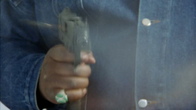 close angle of man's right arm holding uzi, wearing denim jean jacket and ring on pinky finger. he fires the gun several times semi-automatically. insert. - machine gun stock videos & royalty-free footage