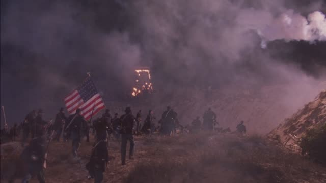 medium angle of burning guard tower and military embankment. see explosions and sparks flying. union troops with us flag charge forward during attack with rifles and bayonets then take cover and lie down. see more union soldiers charge. see smoke from fir - stars and stripes stock videos & royalty-free footage