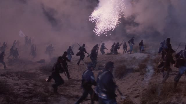 tracking shot of union regiment charging embankment with burning guard tower. see flares fall down and explode on ground, some soldiers killed by explosions. union soldiers run up to sand embankment, then pans quickly left to track another group of soldie - bürgerkrieg stock-videos und b-roll-filmmaterial