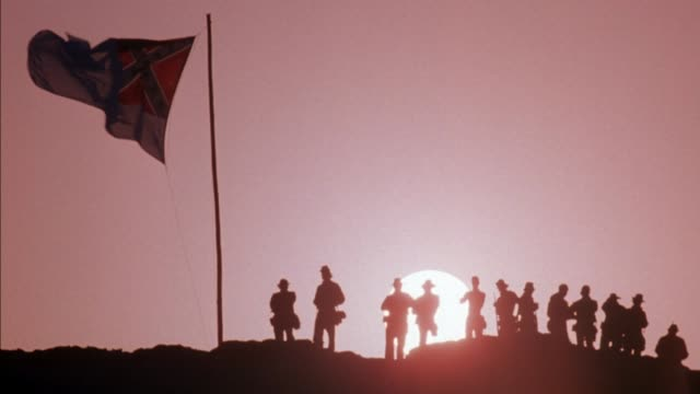 medium angle of twelve soldiers on a hill with flag on flagpole and setting sun. confederate flag flies on pole.  civil war.  civil war. - confederate flag stock videos & royalty-free footage