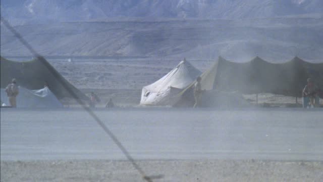 medium angle of army soldiers at a battlefield camp along a road with tents and military truck. see truck driver in helmet. see desert valley and hills in background. see two officers in tan uniforms enter from right and run away from camera as soldiers i - army stock videos & royalty-free footage