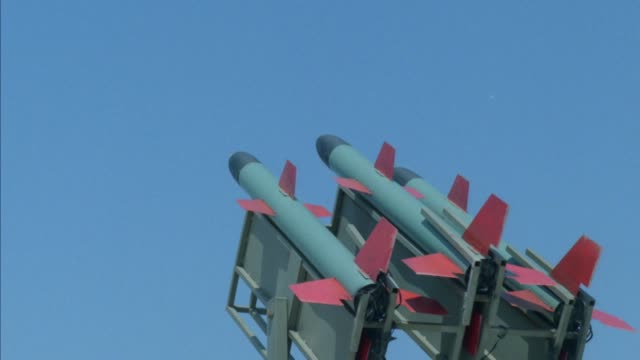 medium shot of three military cruise missiles seen from the rear and pointing up against a clear blue sky. missiles are  light blue or gray color with red wings. see fire and smoke as center missile is launched, then right missile is launched, then left m - ship launch stock videos & royalty-free footage
