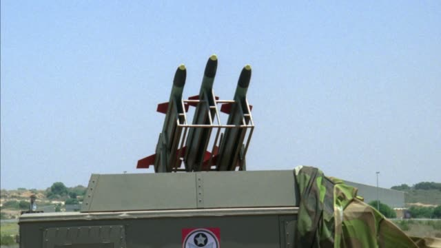 medium shot of three military cruise missiles on top of launch platform or vehicle. missiles are light blue or gray color with red wings. see fire and smoke as center missile is launched, then left missile is launched, then right missile is launched. see - ship launch stock videos & royalty-free footage