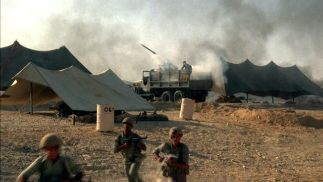 medium angle of army or battlefield camp with tents and military truck with missile launcher. see gray smoke blowing from the right. see seven soldiers in green uniforms with helmets and with guns up a slight slope. see soldier on left point with right ha - tent stock videos & royalty-free footage