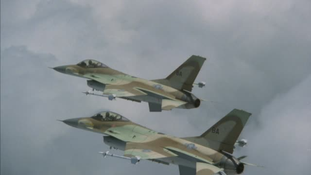 aerial shot of two f-16 fighter jet planes flying in close formation against a background of clouds. see pilot in cockpit of each jet plane. f-16 fighter jets are camouflage colors of tan, brown, green, and black. see white missiles on each wing of each j - general dynamics f 16 falcon stock videos & royalty-free footage