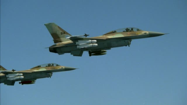 stockvideo's en b-roll-footage met aerial tracking shot of two f-16 fighter jets flying in formation. traveling left to right against clear blue sky.   fairly close to jets.  medium angle.  see missiles and bombs on jets. middle east. - raket wapen