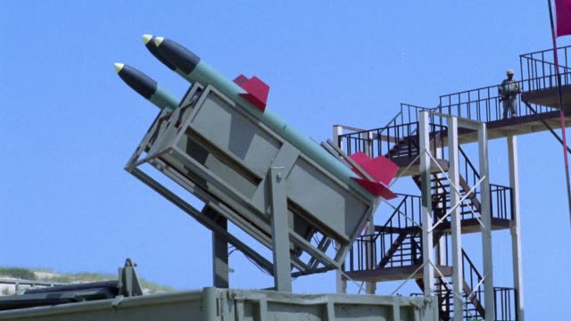 medium angle of missile launcher with three missiles. see each missile launch as several pilots and soldiers run down flight of stairs in background. middle east. - stapellauf stock-videos und b-roll-filmmaterial