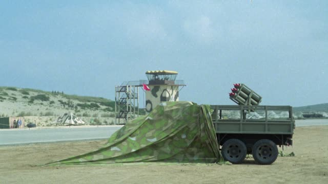 wide angle of camouflage control tower and military truck with missile launcher on top. see six missiles launch and see camouflage tarp covering front of truck. middle east. - ship launch stock videos & royalty-free footage