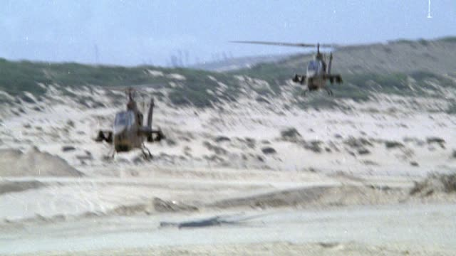 tracking shot of two cobra military helicopters, camera rotates from side to front view but back to side again, helicopters fly over mountainous desert region, at end camera zooms in on cockpit both pilots visible. middle east. attack helicopters. - back to front stock videos & royalty-free footage