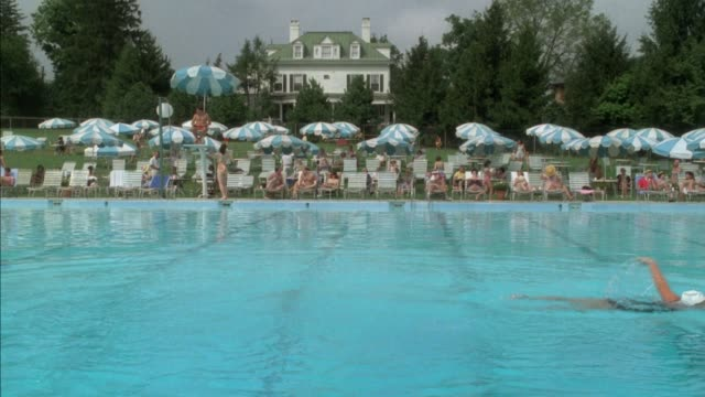 wide angle of a swimming pool with several people diving into pool from off screen diving board overhead. each diver swims to right side. other people swimming in background. women, children, young men lounge poolside beneath umbrellas. 1950s or 1960s era - clubhouse stock videos & royalty-free footage