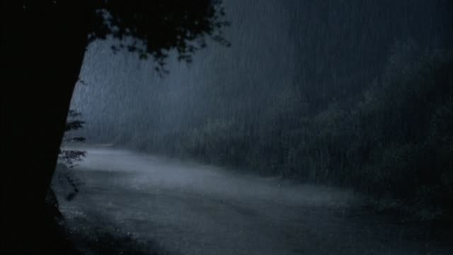 medium angle of country road with heavy rain during storm. two cars with headlights on drive from left to right. - country road stock videos & royalty-free footage