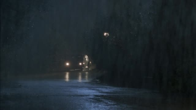 medium angle of country road with heavy rain during storm. see lamp post in background. car with headlights on comes from behind curve forward and goes out of frame to right. another car with headlights does the same. - country road stock videos & royalty-free footage
