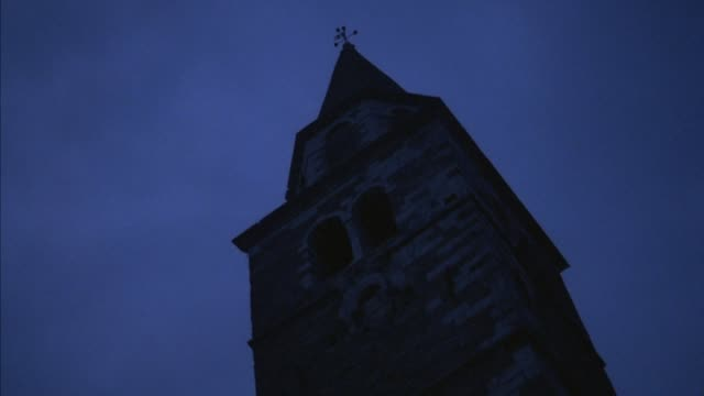 up angle of church bell tower with steeple. see wind vane on top. blue sky, building is very dark. neg cut. - steeple stock videos & royalty-free footage