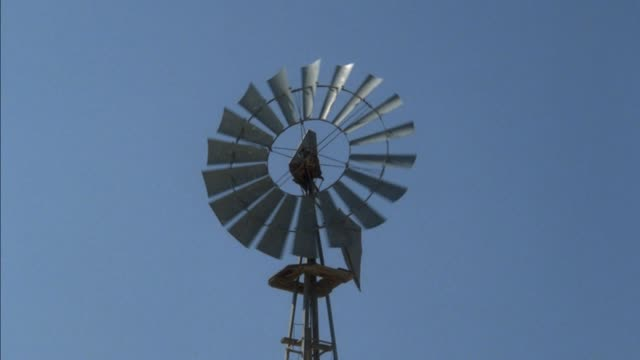 close angle of windmill spinning from wind coming from left. blue sky in back - 1945 stock videos & royalty-free footage