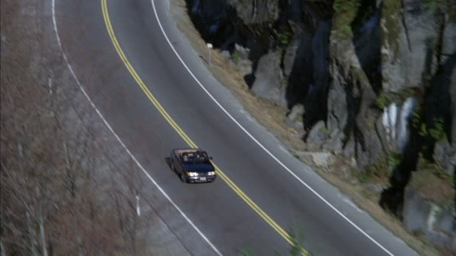 high angle down tracking shot of black convertible driving down mountain road. see rock walls and trees on sides. - convertible overhead stock videos & royalty-free footage