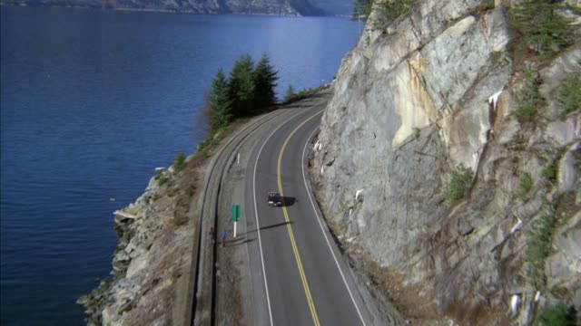 wide high angle down of mountain road next to rock wall on right and blue lake or body of water on left. black convertible drives down road. - blue convertible stock videos & royalty-free footage
