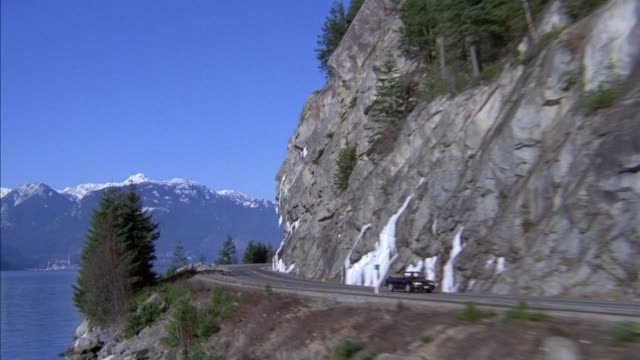 wide high angle down tracking shot of black convertible driving down mountain road next to rock wall on right and blue lake or body of water on left. pulls back, see trees on sides and snowy mountain in far background. - blue convertible stock videos & royalty-free footage