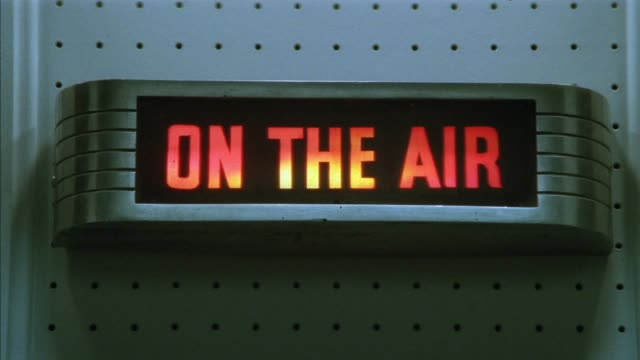 "close angle of ""on the air"" sign on wall in possible radio station.  letters on sign light up in red and yellow and then turns off. insert. neg cut. - radio studio stock videos & royalty-free footage"