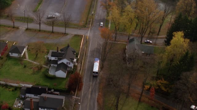 aerial birdseye pov tracking shot of bus driving through streets of suburban town surrounded by autumn trees. bus passes by two story white houses with gray roofs. - zweistöckiges wohnhaus stock-videos und b-roll-filmmaterial