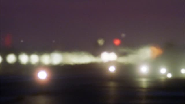medium angle of runway of air force base or military base. pans left and right, rear of jets parked on runway in row. heat wave visible on runway. camera tracks each jet as they take-off. jets blur and become obscure by heat waves. tracks last jet fly to - air force stock videos & royalty-free footage