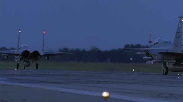 "medium angle of runway of air force base or military base. rear of jet ahead taxiing on runway. second jet with ""eg 33"" on tail follows leading jet. could be f-16 jets. - luftwaffe stock-videos und b-roll-filmmaterial"