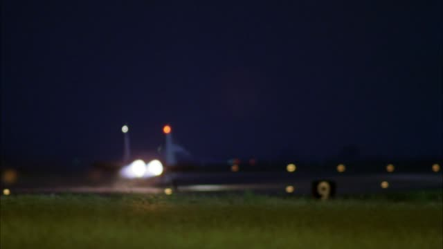 "medium angle side view of lit air force runway at night. camera pans to right and tracks two jets with ""eg 59"" and ""eg 33"" on tails as each take-off from runway. jet lights flare reflect on lens. see ""10"" yard sign and grass in foreground. - air force stock videos & royalty-free footage"