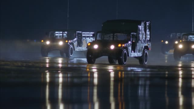 vídeos de stock, filmes e b-roll de medium angle moving pov of military jeeps, pickup trucks and vans moving across to left on air force base or airport runway. - força aérea