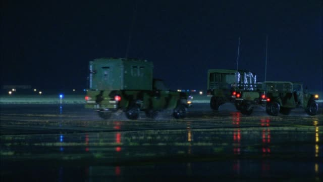 vídeos de stock, filmes e b-roll de medium angle of military jeeps, pickup trucks and vans moving across to right on runway of air force base or airport. - força aérea