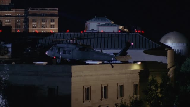 medium angle of building rooftops. black hawk or military helicopter appears from right and lands on corner of rooftop of cement building in front. helicopter then takes off as soldiers on rooftop from building behind shoot at helicopter. explosion happen - hubschrauber stock-videos und b-roll-filmmaterial