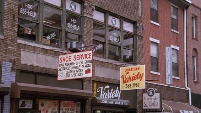 "stockvideo's en b-roll-footage met pan left from stores and signs for ""st. george iv restaurant"", ""jonathan variety"", ""macready & shilts"", ""shoe service"" and ""star photo"" to windows on second floor. see words ""1-800 555-help"" for lawyer service printed on windows. - 1993"