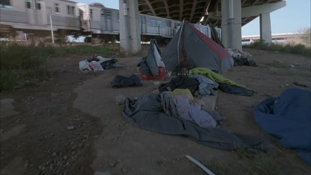 medium angle of tent pitched under freeway overpass. see trash and clothes scattered around. see jean jacket hanging on stick in front of tent and see elevated subway train passing in background. - housing difficulties stock videos & royalty-free footage