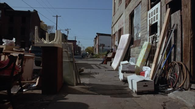 vídeos de stock e filmes b-roll de medium angle of back alley or junkyard filled with old furniture, mattresses and boxes. moving pov from person riding bicycle or motorcycle. see three men sitting on sofa behind building watch as camera approaches. then see side street and buildings in ba - 1993
