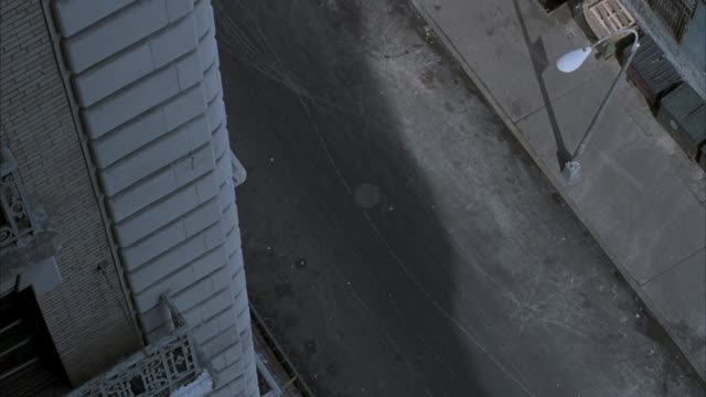 high angle down from about the fourth floor of building looking down over city street. see stone building in left foreground. see two police cars enter on city street on right and park on street. see police officers exit cars and walk out of screen on bot - 1992 stock videos & royalty-free footage