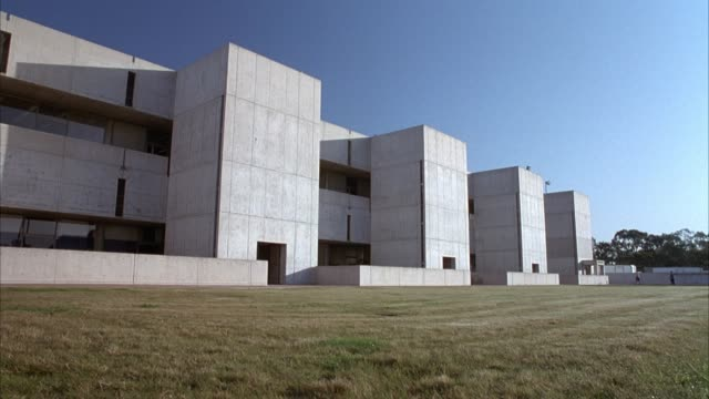 medium angle establishing shot of the salk institute which is a three story modern concrete building. see brown grass lawn leading up to building in foreground. - beton stock-videos und b-roll-filmmaterial