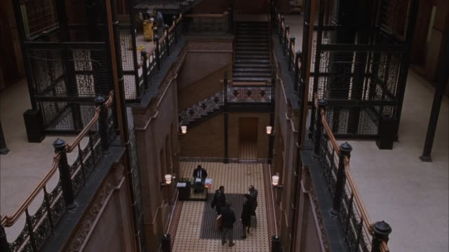 MEDIUM ANGLE PAN UP OF THE ATRIUM LOBBY OF THE BRADBURY BUILDING, OFFICE BUILDING. PANS UP FROM LOBBY UP FIVE STORIES TO SHOW GLASS CEILING. SEE EXPOSED ELEVATOR SHAFTS ALONG EACH SIDE OF BUILDING. COULD BE USED FOR OFFICE BUILDING OF PROFESSIONALS - LAWY