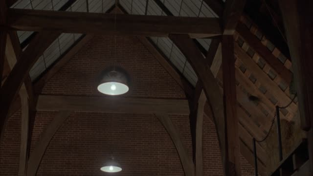 medium angle of interior of wooden barn, stables, house or other structure. see two stories with vaulted ceiling. see pigeons fly about vaulted ceiling. - barn stock videos & royalty-free footage