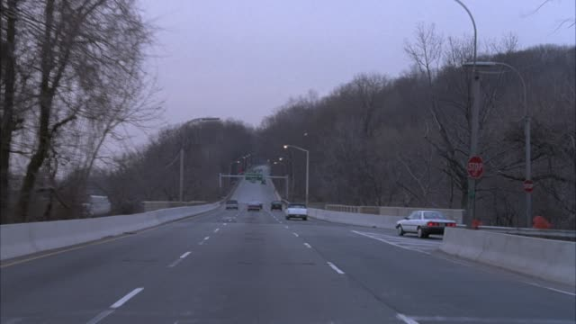 process plate straight forward driving on westside highway or henry hudson parkway on the westside of manhattan on the edge of the hudson river. highway is three lanes all moving north. see other cars driving on road. see bare trees on right with apartmen - bare tree stock-videos und b-roll-filmmaterial