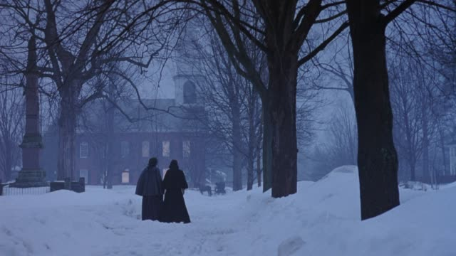 medium angle of church with bare trees surrounding area. snow covers ground, overcast. two women wearing bonnets appears from right and walk toward church. - xix secolo video stock e b–roll