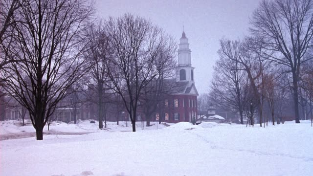 medium angle of church with bare trees surrounding area. snow covers ground, overcast. horse drawn carriage passes to left as two women wearing bonnets appears from right and walk toward church. - compartment stock videos & royalty-free footage
