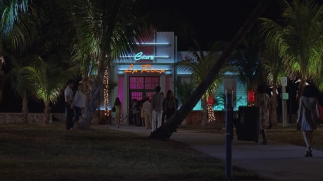 """stockvideo's en b-roll-footage met wide angle of nightclub entrance with adults entering. neon sign reads """"club la roca"""" above door, palm trees surround nightclub. some traffic passes to right. bars. - roca"""