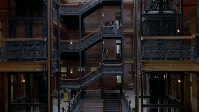 MEDIUM ANGLE PAN UP OF ATRIUM LOBBY OF BRADBURY BUILDING, OFFICE BUILDING. SEE ELEVATOR SHAFTS ON SIDES, STAIRCASES FROM MULTIPLE SIDES. GLASS CEILING ON TOP. COULD BE USED FOR OFFICE BUILDING OF PROFESSIONALS - LAWYERS, DOCTORS, ARCHITECTS, BUSINESSMEN.