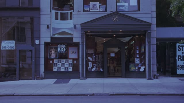 medium angle of storefront of bookstore. some cars pass by in foreground. - bookstore stock videos & royalty-free footage