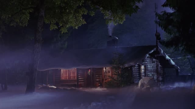 medium angle of log cabin in woods or forest. snow of roof and ground. see smoke rise from chimney or smoke stack. lit from inside, christmas wreath on door. - capanna di legno video stock e b–roll
