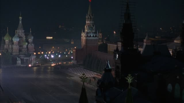 wide angle of  st. basil's cathedral on far left. see building opposite cathedral with spire, possibly church. see motorcade of about 15 cars with police escort enter red square in foreground from around church building and turn left toward front. police - spire stock videos & royalty-free footage