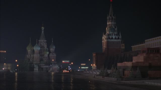 wide angle of  st. basil's cathedral in center background. see building to right of cathedral with spire, possibly church. see motorcade of about 15 cars with police escort enter red square from distance and move toward front. police cars have bizbar ligh - spire stock videos & royalty-free footage