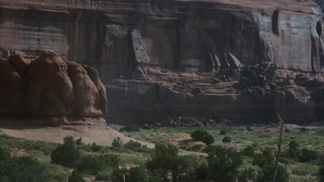 vidéos et rushes de pan down then left to right of native american (apache) village. see red sandstone canyon, smoke from campfire, women, children, horses, and men. see grass huts or dwellings. - cabane structure bâtie