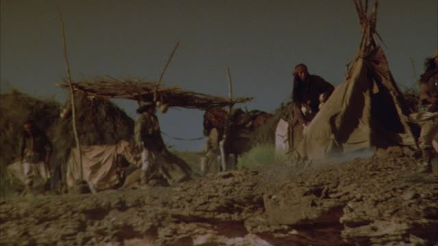 stockvideo's en b-roll-footage met medium angle of native american village or campsites. see native american (apache) men moving about with horses and rifles. see tee pees or tents. see campfire smoke and clothing being blown by the wind. - amerikaans indiaanse etniciteit