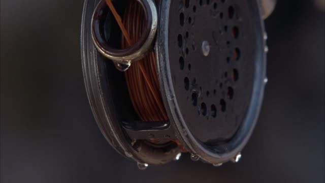 CLOSE ANGLE OF REEL OF FISHING POLE. SEE WATER DROPLETS ON REEL AND ORANGE-BROWN FISHING LINE. SEE FISHING LINE BEING RAPIDLY PULLED FROM REEL.